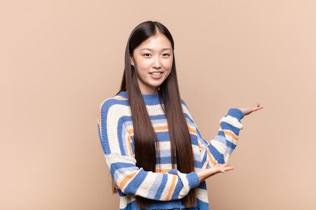 Asiatische junge frau, die stolz und zuversichtlich lächelt und sich glücklich und zufrieden fühlt