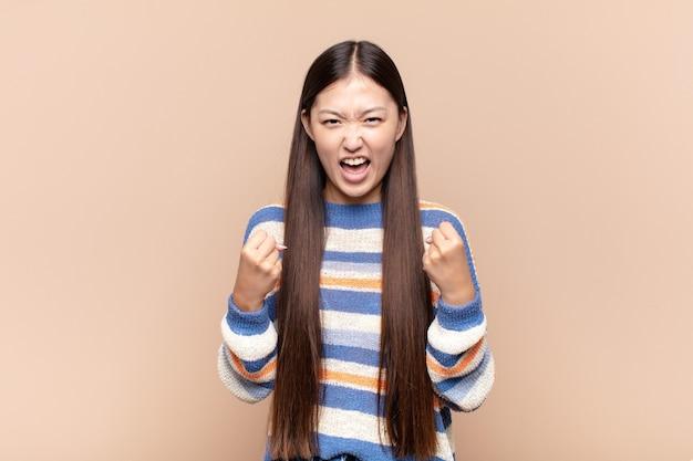 Asiatische junge frau, die triumphierend schreit, lacht und sich glücklich und aufgeregt isoliert fühlt