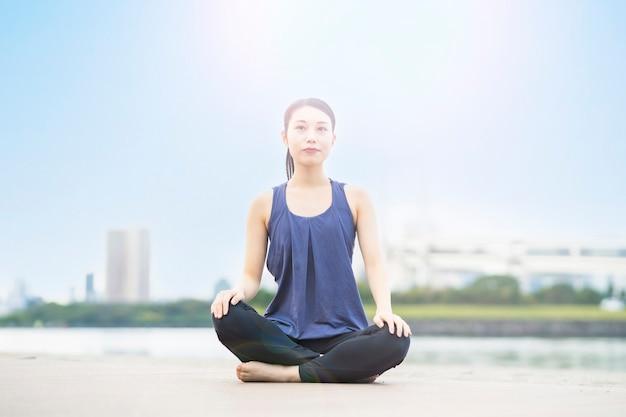 Asiatische junge frau, die yoga am strand in der stadt tut
