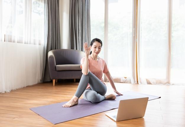 Asiatische junge frau, die yoga auf matte praktiziert, während sie zu hause vor ihrem laptop sitzt.