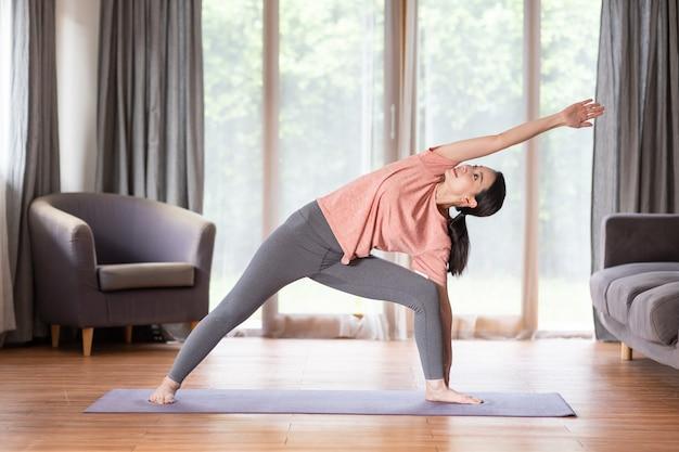 Asiatische junge frau, die yoga auf übungsmatte im wohnzimmer praktiziert, während sie zu hause ruht.