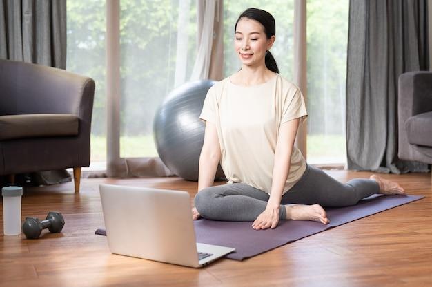 Asiatische junge frau, die yoga mit ihrem laptop-computer beim sitzen auf matte zu hause tut.