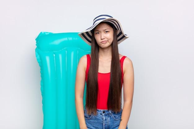 Asiatische junge frau fühlt sich verwirrt und zweifelhaft, wundert sich oder versucht zu wählen oder eine entscheidung zu treffen. sommerkonzept