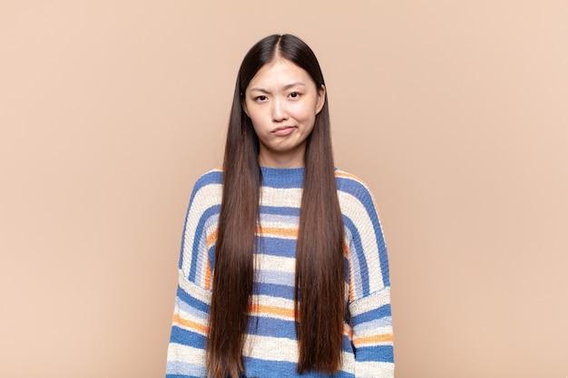 Asiatische junge frau fühlt sich verwirrt und zweifelhaft, wundert sich oder versucht zu wählen oder eine entscheidung zu treffen.