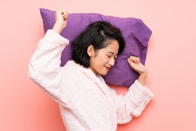 Asiatische junge frau in den pyjamas gähnend