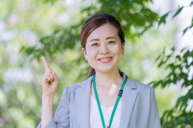 Asiatische junge frau in einem geschäftsoutfit, das oben zeigt
