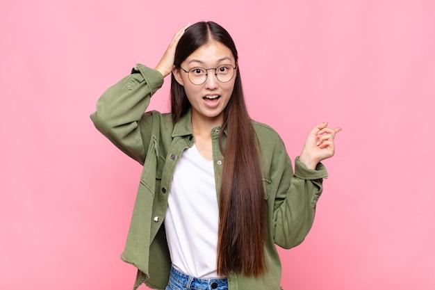 Asiatische junge frau lacht, sieht glücklich, positiv und überrascht aus und verwirklicht eine großartige idee, die auf seitlich zeigt