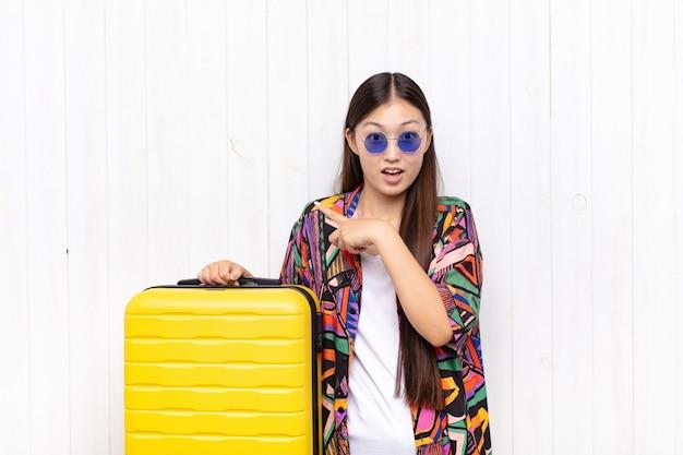 Asiatische junge frau lacht, sieht glücklich, positiv und überrascht aus und verwirklicht eine großartige idee, die auf seitlichen kopierraum zeigt. urlaubskonzept