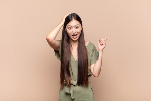 Asiatische junge frau lacht, sieht glücklich, positiv und überrascht aus und verwirklicht eine großartige idee, die auf seitlichen kopierraum zeigt