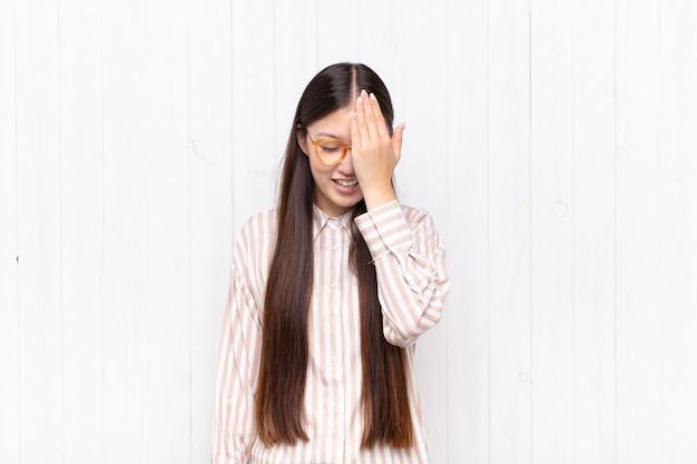 Asiatische junge frau lacht und schlägt auf die stirn, als würde sie sagen, oh! ich habe es vergessen oder das war ein dummer fehler
