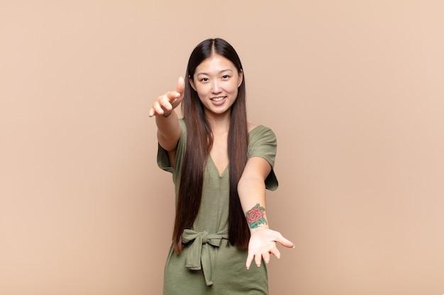 Asiatische junge frau lächelt fröhlich und gibt eine warme, freundliche