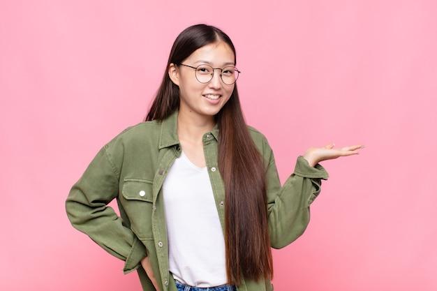 Asiatische junge frau lächelt, fühlt sich sicher, erfolgreich und glücklich, zeigt konzept oder idee auf kopienraum auf der seite