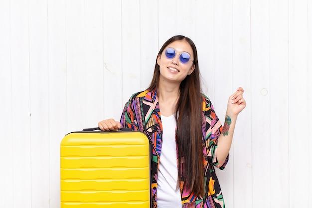Asiatische junge frau lächelt, fühlt sich sorglos, entspannt und glücklich, tanzt und hört musik, hat spaß auf einer party. urlaubskonzept