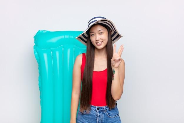 Asiatische junge frau lächelt und sieht freundlich aus, zeigt nummer drei oder dritte mit der hand nach vorne, countdown. sommerkonzept