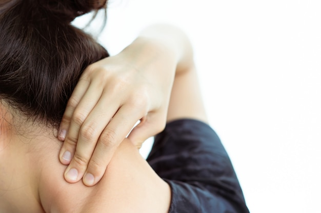 Asiatische junge frau mit einem gesundheitsproblem im nacken oder nacken, bürosyndrom bei jungen menschen. gesundheit bei berufstätigen frauen deprimiert. frau, die versucht, sich an hals und schultern zu massieren.