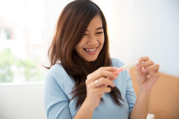 Asiatische junge frau mit einem testpack in der hand, glücklich lächelnd