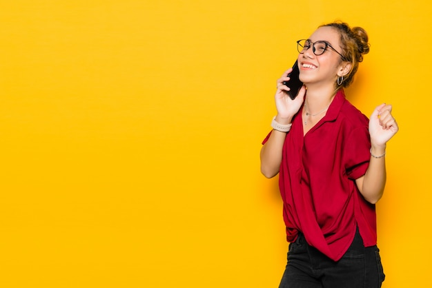 Asiatische junge frau mit glücklichem gesicht, das auf smartphone spricht