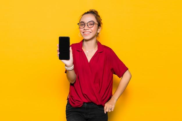 Asiatische junge frau mit glücklichem gesicht und haltendem smartphone