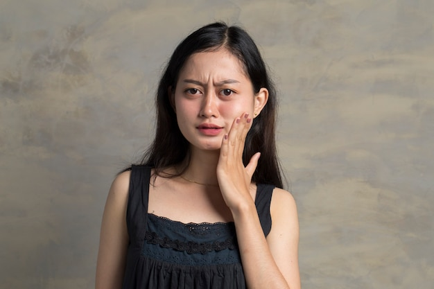 Asiatische junge frau mit zahnschmerzen