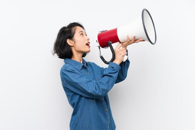 Asiatische junge frau über das schreien durch ein megaphon