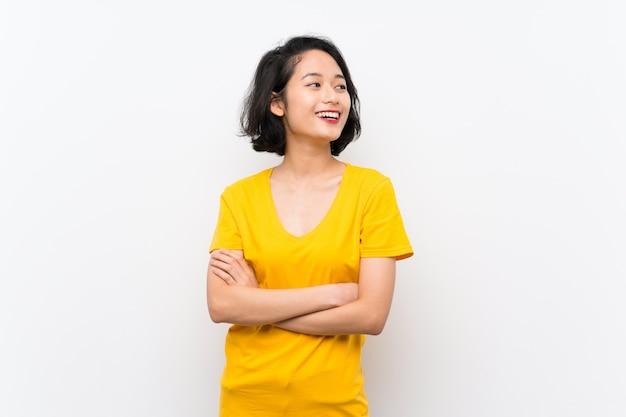 Asiatische junge frau über dem lokalisierten weißen hintergrund glücklich und dem lächeln