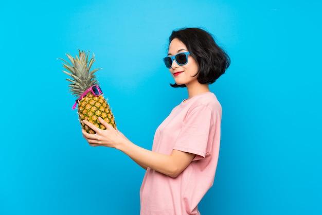 Asiatische junge frau über der lokalisierten blauen wand, die eine ananas mit sonnenbrille hält