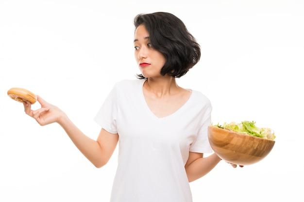 Asiatische junge frau über getrenntem hintergrund mit salat und krapfen