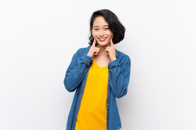 Asiatische junge frau über getrenntem weißem lächeln mit einem glücklichen und angenehmen ausdruck