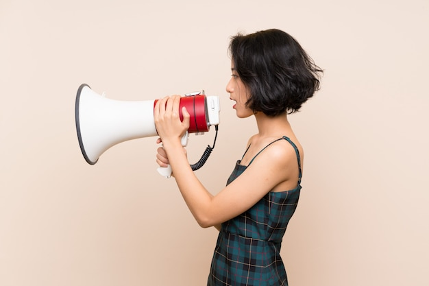 Asiatische junge frau über lokalisierter gelber wand schreiend durch ein megaphon