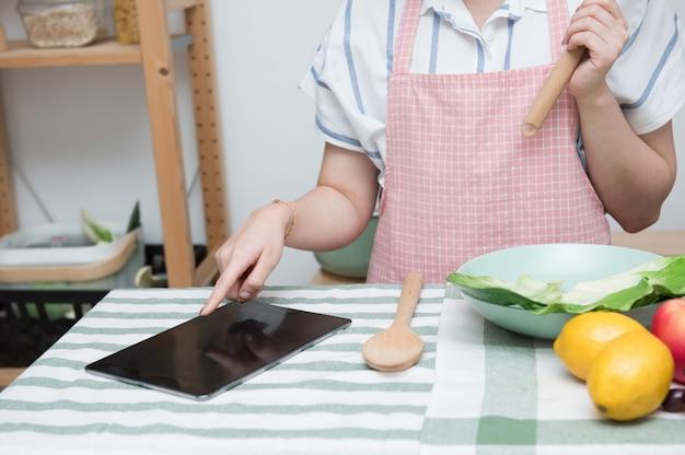 Asiatische junge frau verwenden finger folie auf tablet-bildschirm vorbereiten zutaten für das kochen folgen kochen online-videoclip auf der website in der küche, soziale distanzierung, zu hause bleiben und von zu hause aus arbeiten konzept.