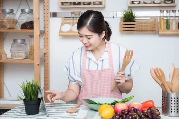 Asiatische junge frau verwenden fingerrutsche auf tablettbildschirm bereiten zutaten zum kochen vor