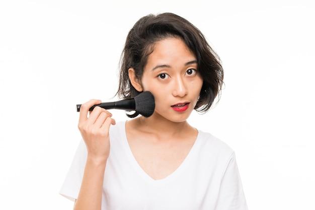 Asiatische junge frau vorbei lokalisiert mit make-upbürste
