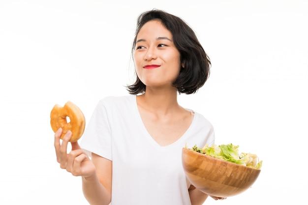 Asiatische junge frau vorbei lokalisiert mit salat und donut