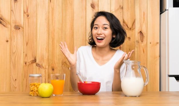 Asiatische junge frau, welche die frühstücksmilch unglücklich und mit etwas frustriert isst