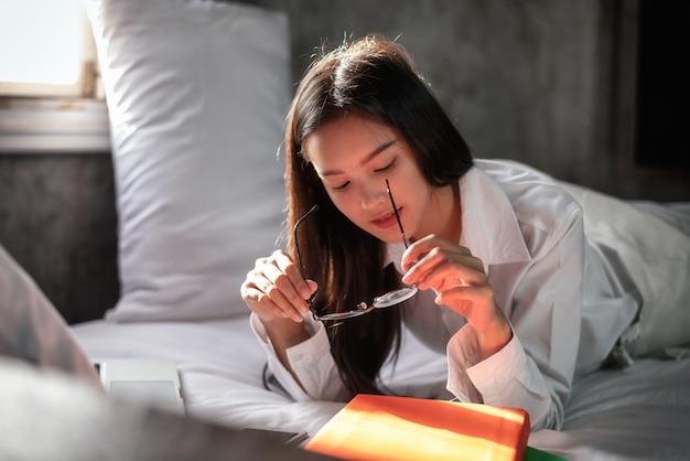 Asiatische junge frau, wenn ein buch auf bett gelesen wird