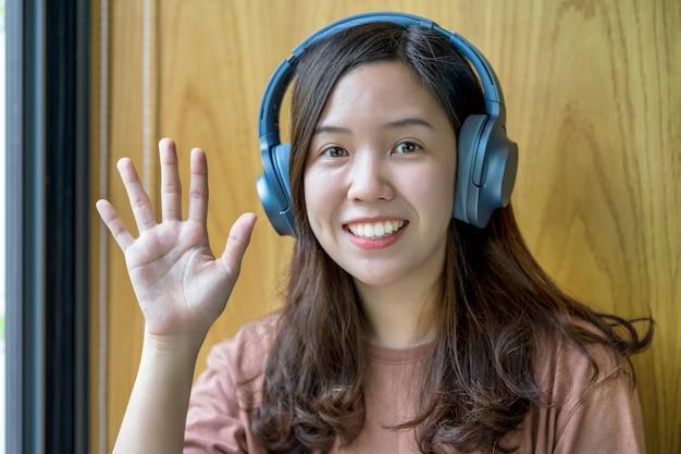 Asiatische junge frau winkt mit der hand, um hallo zu sagen, wenn sie einen videoanruf mit einem freund mit sozialer distanzierung macht