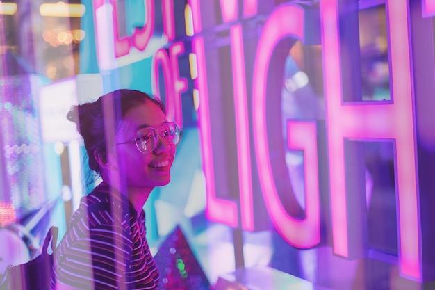 Asiatische junge frauen, die gläser tragen, betrachten neonlichter