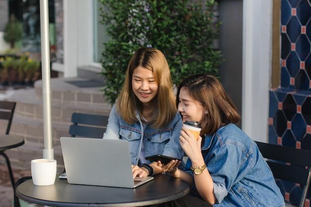 Asiatische junge frauen in der intelligenten zufälligen kleidung, sendend e-mail auf laptop und trinkenden kaffee während