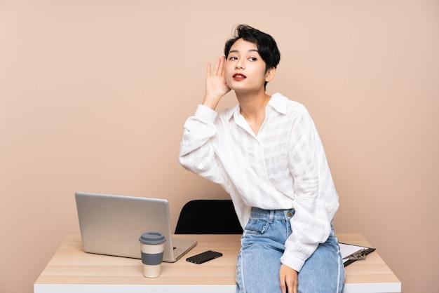 Asiatische junge geschäftsfrau an ihrem arbeitsplatz, der etwas hört