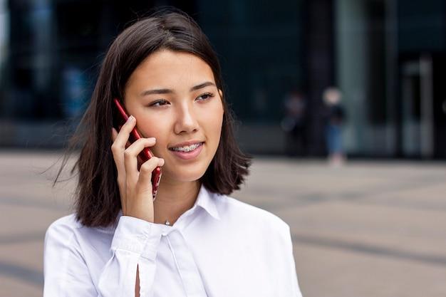 Asiatische junge geschäftsfrau, die auf handy spricht
