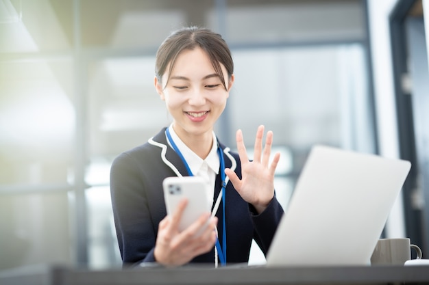 Asiatische junge geschäftsfrau, die mit dem bildschirm ihres smartphones spricht