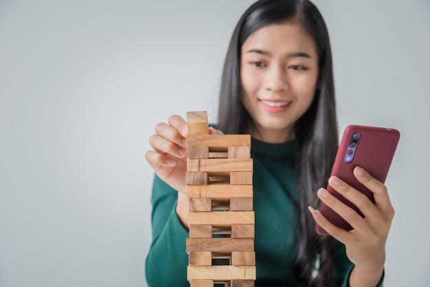 Asiatische junge geschäftsfrau, die mit holzklötzen spielt und smartphone verwendet