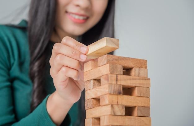 Asiatische junge geschäftsfrau, die mit holzklötzen spielt