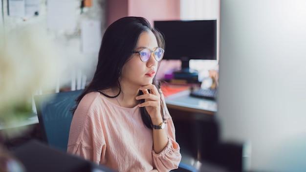 Asiatische junge geschäftsfrau, die vom hauptbüro arbeitet.