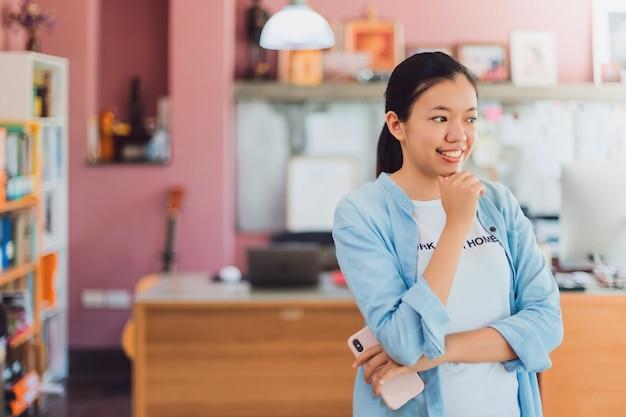 Asiatische junge geschäftsfrau, die vom hauptbüro steht und arbeitet.