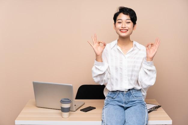 Asiatische junge geschäftsfrau in ihrem arbeitsplatz, der ein ok-zeichen mit den fingern zeigt