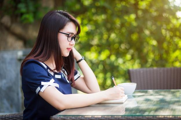 Asiatische junge geschäftsfrau schreiben eine anmerkung