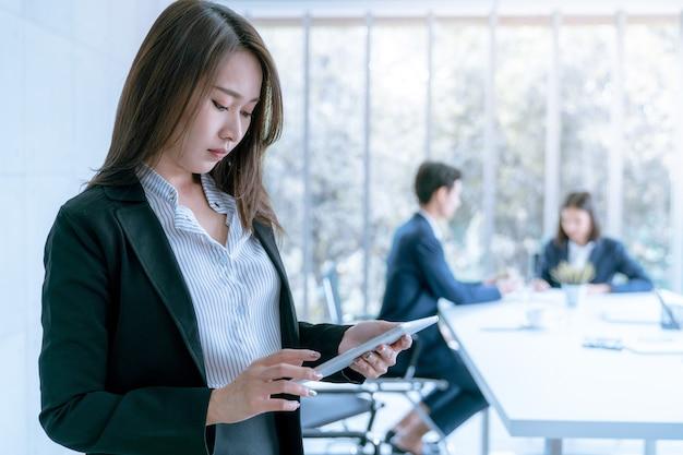 Asiatische junge geschäftsfrau, wenn tablette verwendet wird, um über vermarktungsplan zu arbeiten