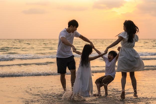 Asiatische junge glückliche familie genießen abends urlaub am strand. vater, mutter und kind entspannen sich beim spielen zusammen in der nähe des meeres, wenn silhouette sonnenuntergang. lifestyle reise urlaub urlaub sommer konzept.
