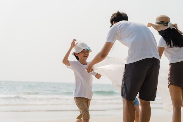 Asiatische junge glückliche familienaktivisten, die plastikmüll am strand sammeln. freiwillige aus asien helfen dabei, die natur sauber zu halten und müll aufzuheben. konzept über umweltschutzprobleme.